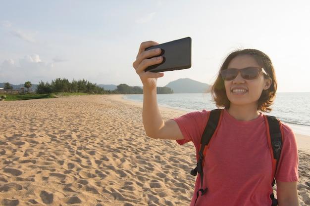 アジアの女性は海で旅行休暇の携帯電話を使用しています。