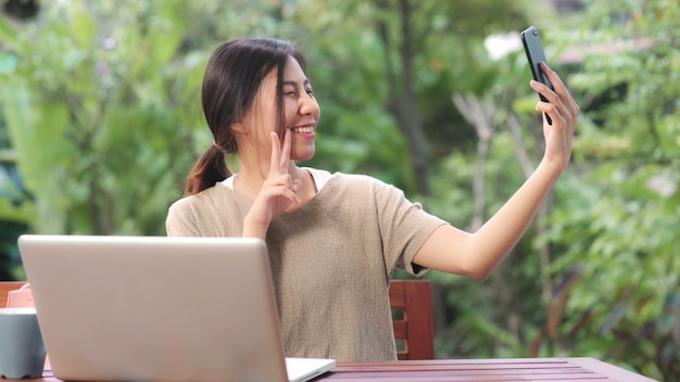 Asian woman using mobile phone selfie post in social media, female relax feeling happy showing shopping bags sitting on table in the garden in morning.
