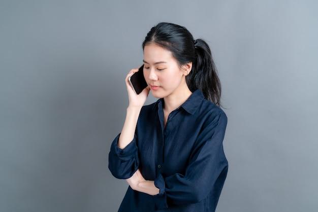 Азиатская женщина с помощью мобильного телефона разговаривает по бизнесу, изолированному на сером фоне