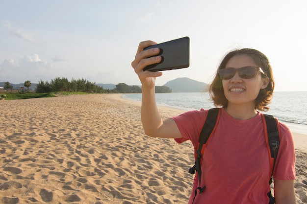 Asian woman using mobile phone on travel vacation at ocean.
