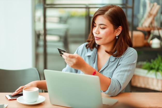 커피 숍에서 온라인 결제 쇼핑을 위해 신용 카드 및 노트북 컴퓨터와 휴대 전화를 사용하는 아시아 여자