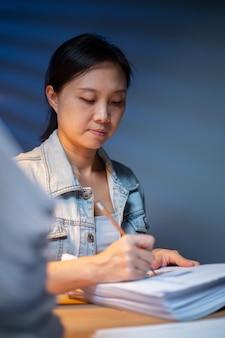 Азиатская женщина, использующая карандаш для заметки о финансах отчета с сверхурочной работой в офисе. работает поздно для четкого документа в ночное время. сверхурочная работа допоздна.
