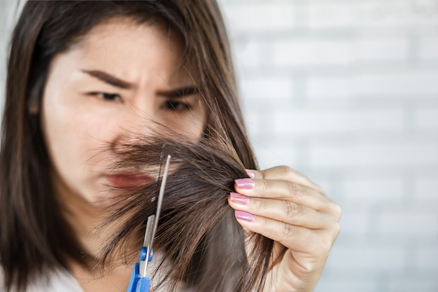 Asian woman using scissors cut split ends of damaged hair