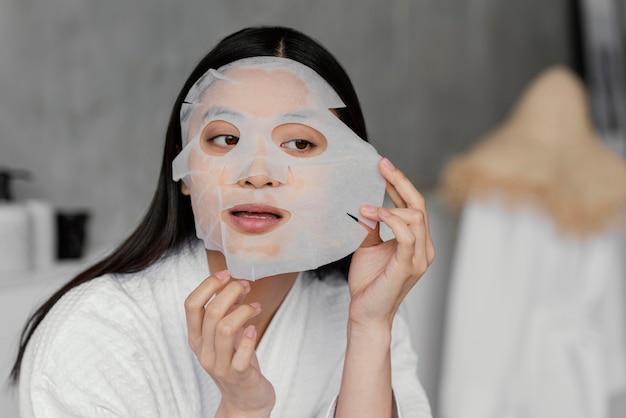 Donna asiatica che usando una maschera del foglio