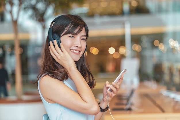 Азиатская женщина с помощью смарт-мобильного телефона и прослушивания музыки через наушники крышки головы