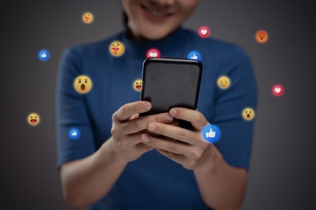 Азиатская женщина с помощью смартфона для социальных сетей с пузырем смайлика. изолированные