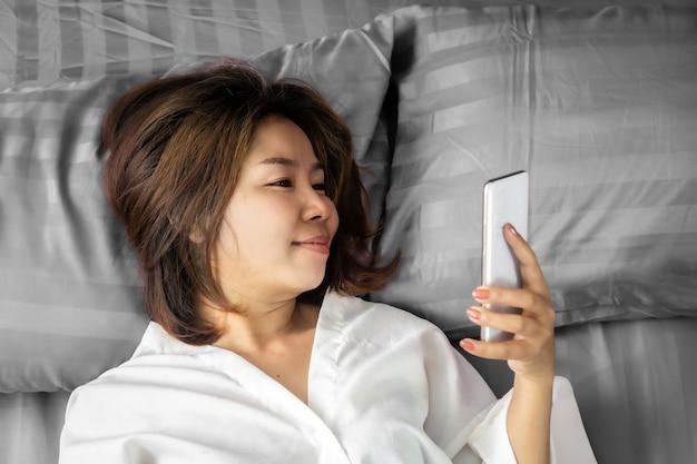 ベッドでスマートフォンを使用してアジアの女性