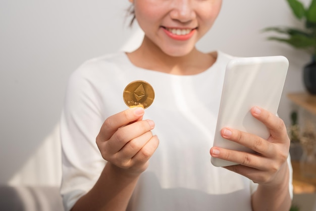 Asian woman using smart phone to pay online by bitcoin