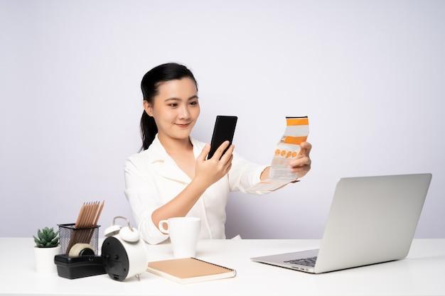 온라인 결제 유틸리티 청구를 위해 스마트폰 스캔 qr 코드를 사용하는 아시아 여성.