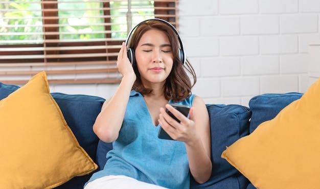 스마트폰을 사용하고 헤드폰에 연결하여 음악을 듣는 아시아 여성