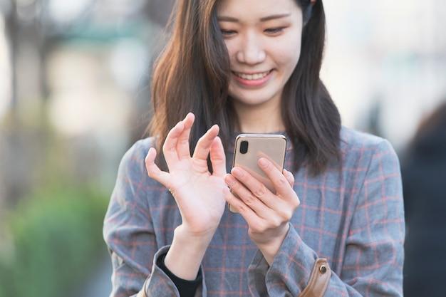 スマートフォンを使用して写真を撮り、アプリケーションを使用するアジアの女性