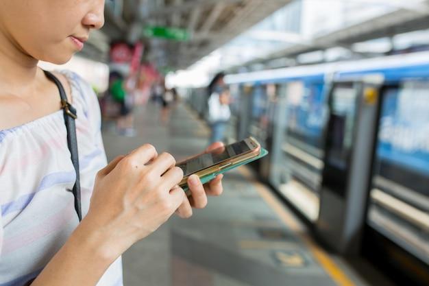 Азиатская женщина, использующая смартфон для поиска данных и информации.
