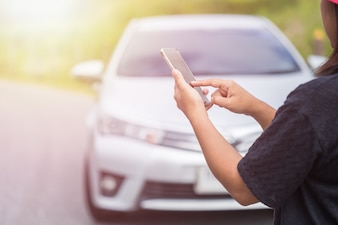 Asian woman using smartphone in front of her broken car on the road