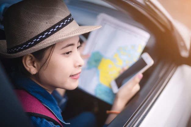 Asian woman using smartphone and map between driving car on road trip