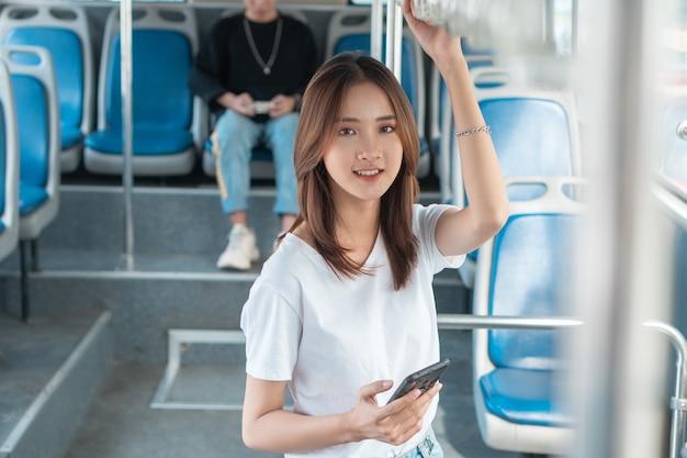 버스에서 스마트폰을 사용하는 아시아 여성