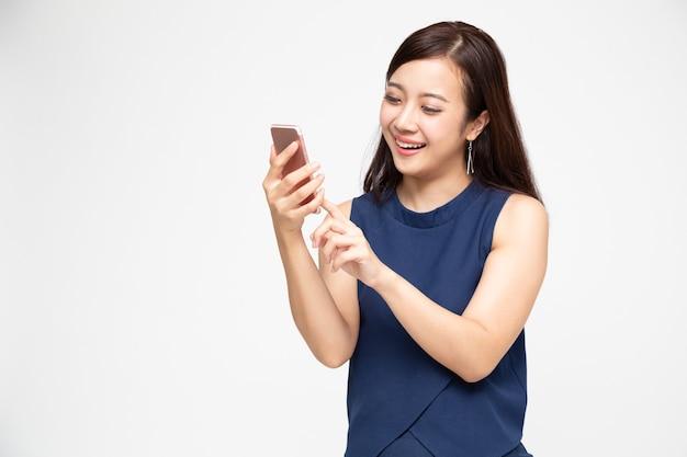 흰 벽에 스마트 폰을 사용 하여 아시아 여자