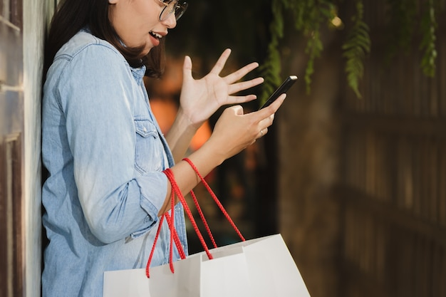 Asian woman using smartphone and shopping with happy in free time.