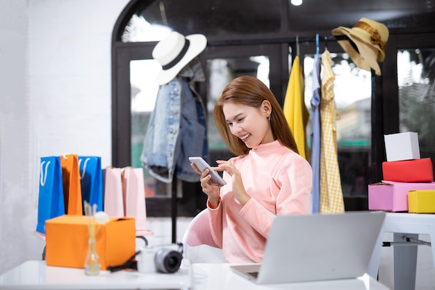 Asian woman using a smartphone and smiling while sitting in workshop