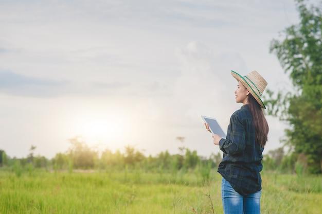 Asian woman using a tablet on a farm field