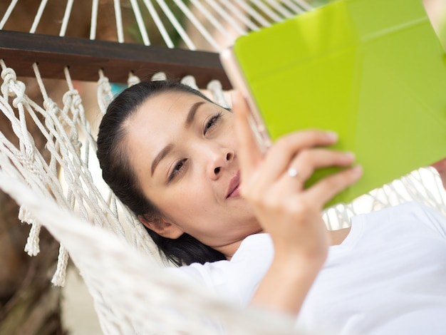 Asian woman using tablet and relax on hammock on the beach in thailand
