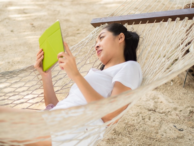 Asian woman using tablet and relax on hammock on the beach
