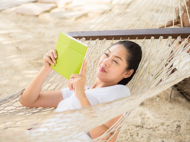 Asian woman using tablet and relax on hammock on the beach.