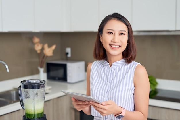 タブレットを使用して、キッチンで果物と野菜を使ったスムージーを作るレシピを見つけるアジアの女性。