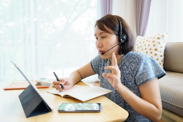 アジアの女性がタブレットを使用して、レッスンオンラインコース通信を見て