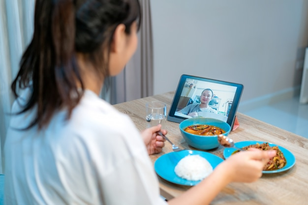 Asian woman virtual happy hour meeting dinner and eating food online together