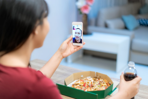 Asian woman virtual happy hour meeting dinner and eating pizza food online together with her boyfriend in video conference with digital tablet