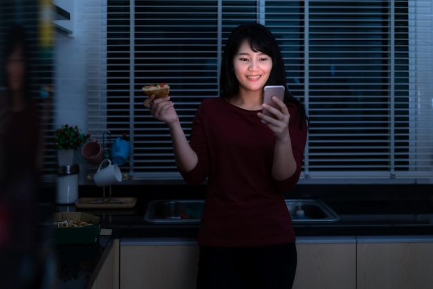 Asian woman virtual happy hour meeting and eating delivery pizza from the box online with friend or taking photo using mobile phone camera in kitchen at night during time of home isolation.