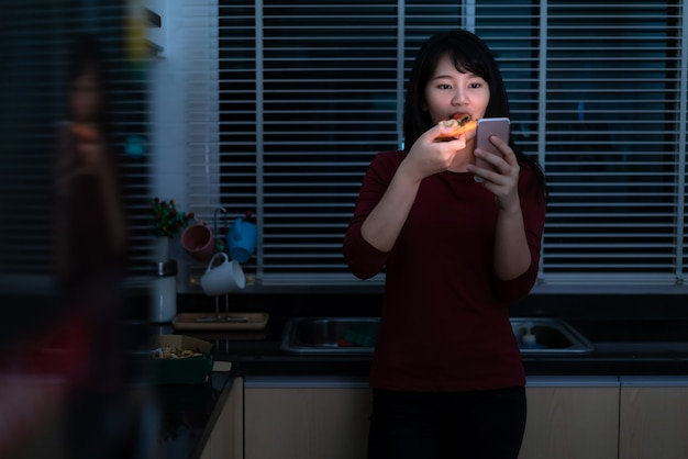 Asian woman virtual happy hour meeting and eating delivery pizza from the box online with friend or taking photo using mobile phone in kitchen at night during time of home isolation.