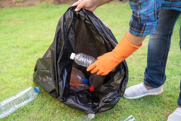 アジアの女性ボランティアが公園のゴミ袋のゴミ箱に水ペットボトルを運ぶ