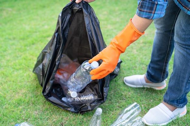アジアの女性ボランティアが公園のゴミ袋のゴミに水ペットボトルを運ぶ
