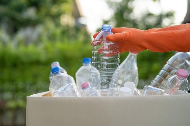 アジアの女性ボランティアが水ペットボトルをゴミ箱のゴミ箱に運びます