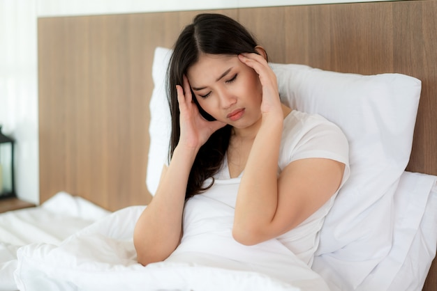 Asian woman wake up on her bed holding their hand from headache and looking unhappy