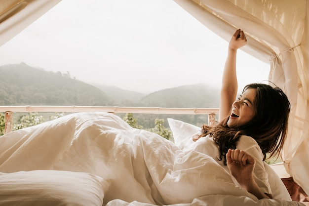 Asian woman wake up in tent and looking at mountain view in sunset time