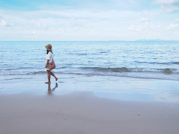 Asian woman walking alone on sand along the beach in the morning.