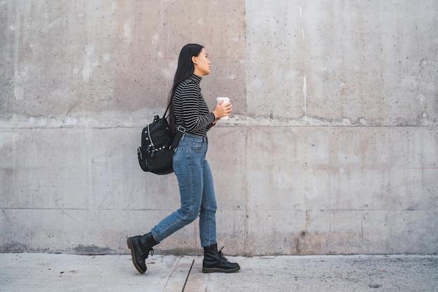 ウォーキングと一杯のコーヒーを保持しているアジアの女性。