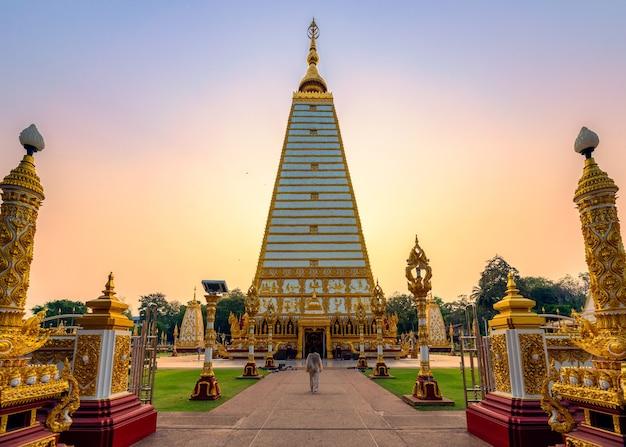 タイ、ウボンラチャタニのワットプラタートノンブアでカラフルな夕方の空と黄金の仏舎利塔スリマハポーチェディを歩くアジアの女性