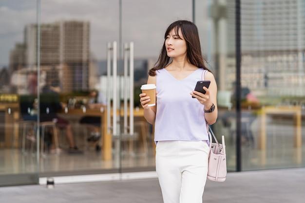 街を歩いて携帯電話を使用し、コーヒーの紙コップを持っているアジアの女性