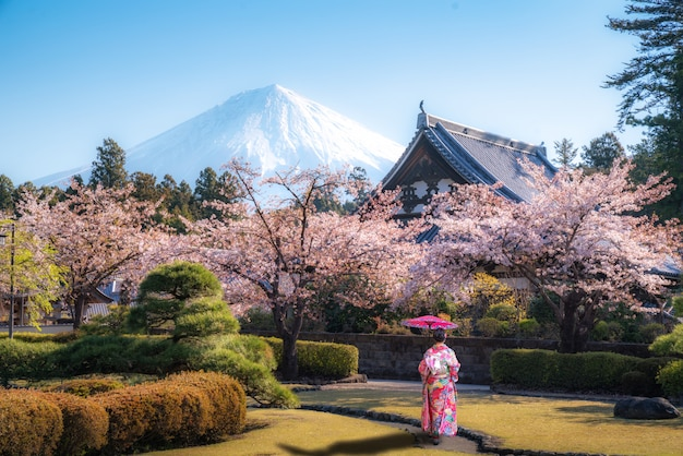 Asian woman walking in temple with mt. fuji in japan