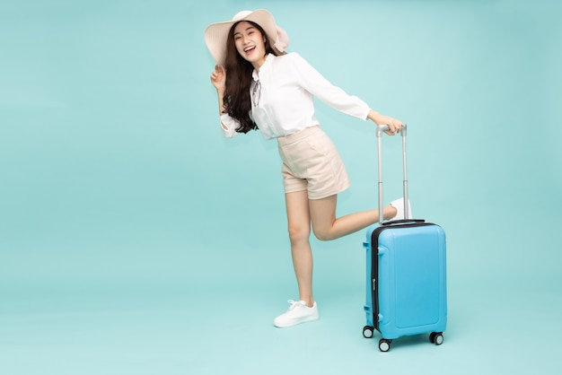Asian woman walking with suitcase isolated on green background