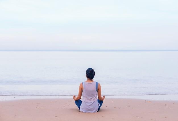 Азиатская женщина разогревает и играет упражнения йоги и медитирует на пляже у моря на фоне утреннего неба.