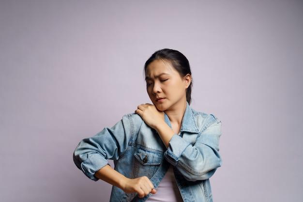 アジアの女性は体の痛みで体に触れ、孤立して立っていました。