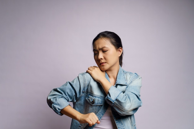 Asian woman was sick with body pain touching her body and standing isolated.