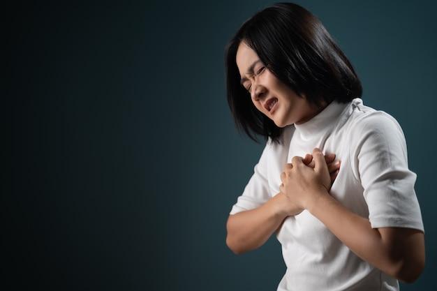 Азиатская женщина была больна болью в груди и стояла изолированной над синим