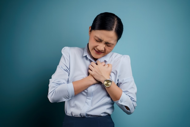 Asian woman was sick with chest pain standing isolated on blue.