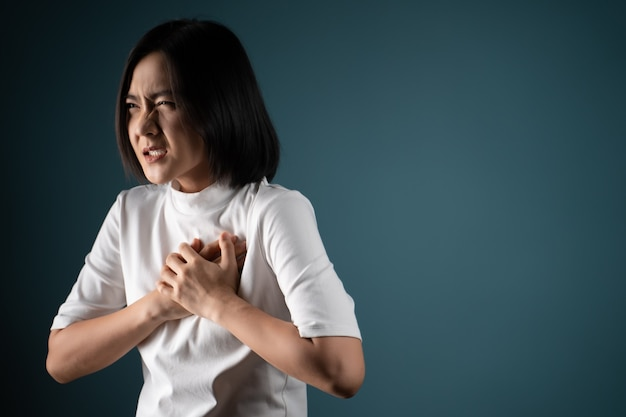 Asian woman was sick with chest pain and standing isolated over blue