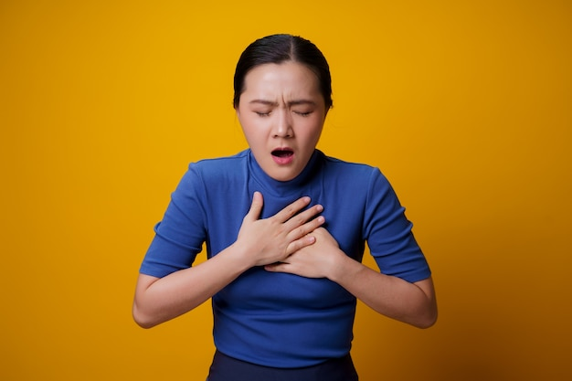 Asian woman was sick with chest pain standing yellow.